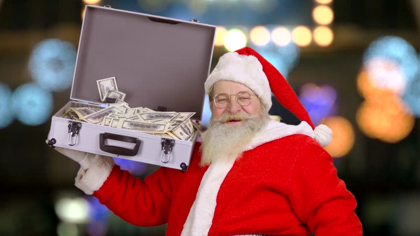 Santa holding suitcase with money. Santa Claus showing thumb up. Christmas  and capitalism.