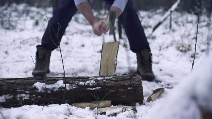 Lumberjack chopping wood in the winter, super slow motion, shot at 240fps