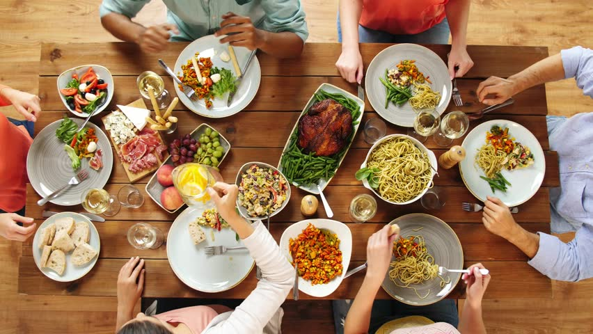 Eating and leisure concept - group of people having dinner at table with food | Shutterstock HD Video #32554975