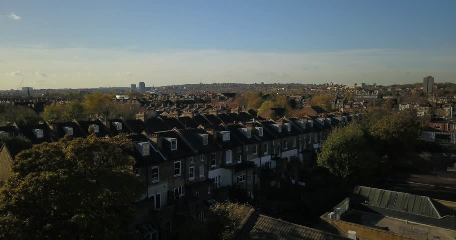 Aerial drone footage, sweeping shot of residential buildings in North London, UK.