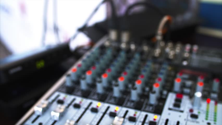 Close view of blurred sound console with many indicators, sliders, and buttos and closeup of two microphones | Shutterstock HD Video #32577874