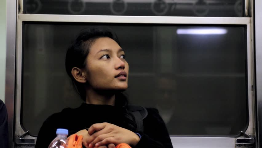 Asian girl is on the train. A young woman is passenger in a subway. Young traveler sitting on a metro train.