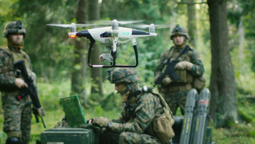 In the Military Staging Base Army Engineer and Soldiers Fly Military Grade Industrial Drone for their Reconnaissance/ Surveillance Mission/ Operation. Theater of Operation is in Forest Area. 4K UHD.