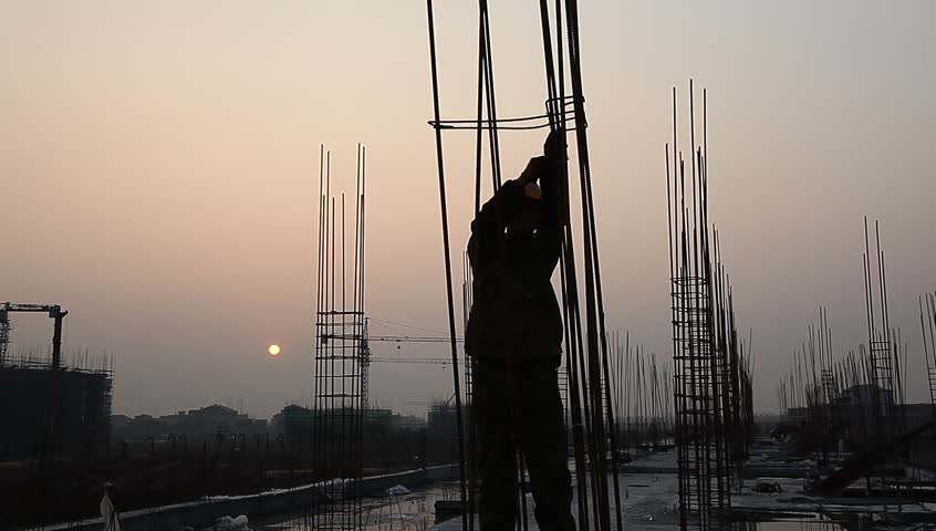 worker working with concrete reinforce iron near sunset