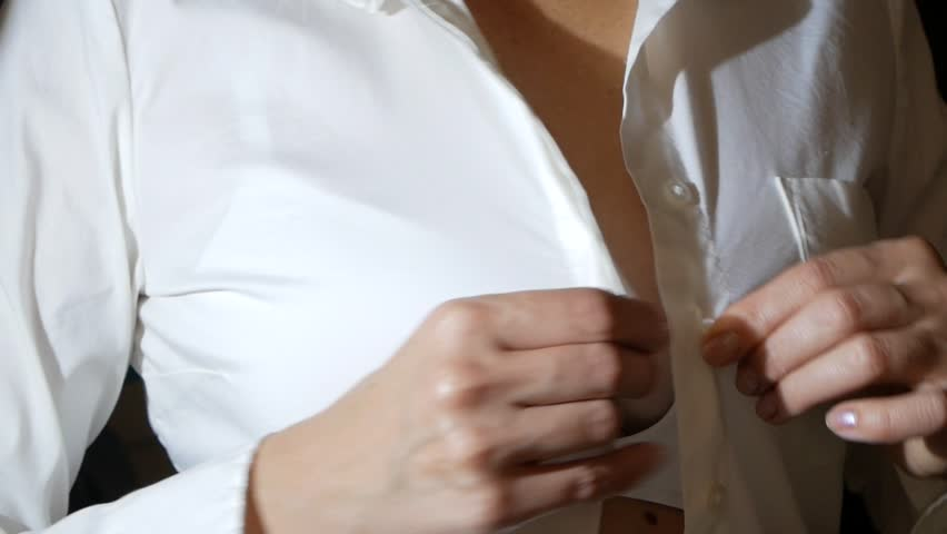 Close-up, details. a woman unfastens the top button on her white shirt, removes it. 4k, slow motion