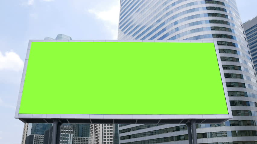billboard with a blank green screen mock-up in front of office building in business district on a busy day, time lapse. footage for advertising background