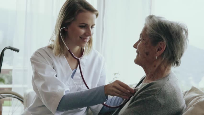 Health visitor and a senior woman during home visit. A female nurse or a doctor examining a woman. Slow motion. Royalty-Free Stock Footage #32667007