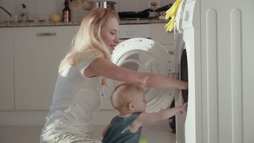 Young mother with baby sitting on floor front washing machine and putting dirty laundry into. Young mother using washing machine for wash