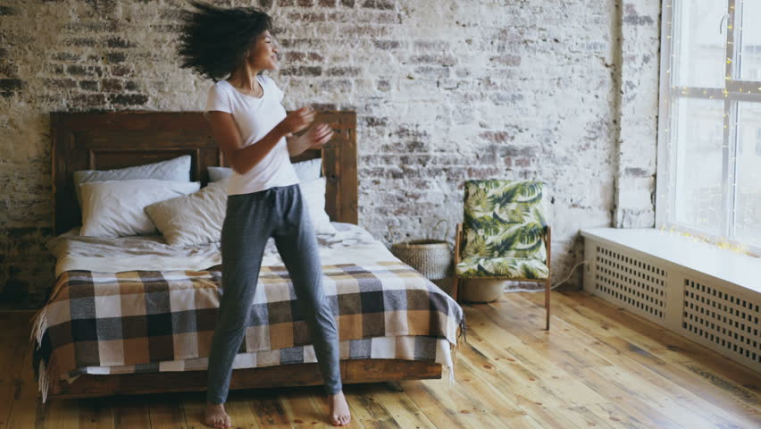 Attractive mixed race joyful girl have fun dancing near bed at modern apartment