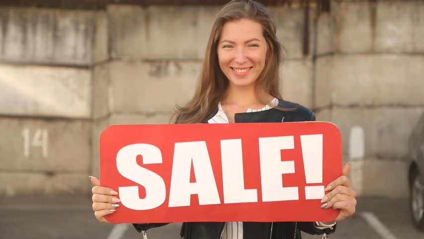 "The girl shows a sign ""SALE"". 