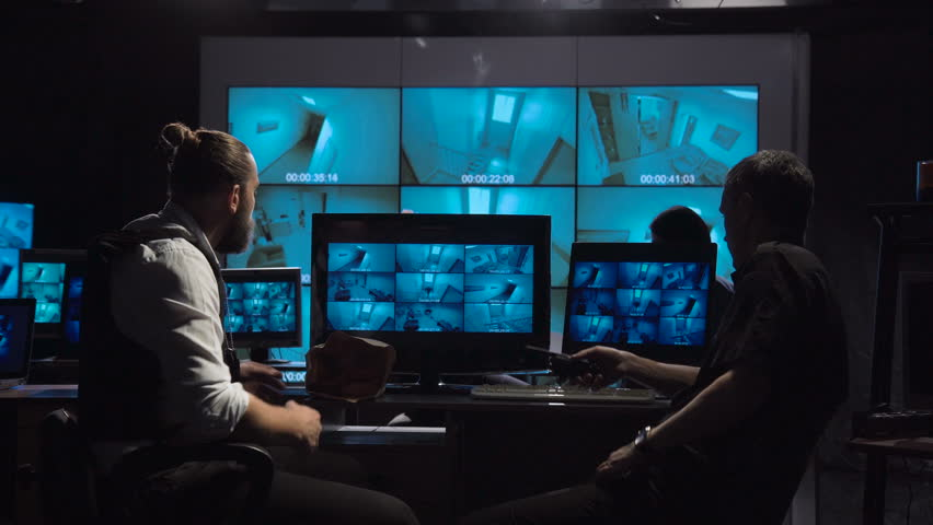 A special forces and policemen surveillance team in a modern office with large live screens.