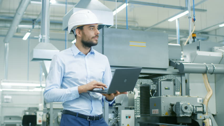 Chief Engineer in the Hard Hat Walks Through Light Modern Factory While Holding Laptop. Successful, Handsome Man in Modern Industrial Environment. Shot on RED EPIC-W 8K Helium Cinema Camera.