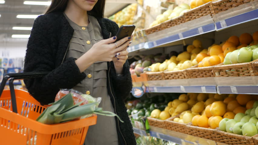 Shopping, technology, sale, consumerism and people concept - woman with smartphone and food basket at supermarket or store | Shutterstock HD Video #32724406