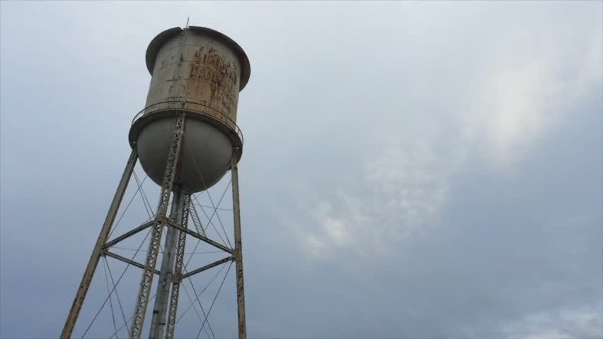 Water tower next to abandoned decaying building surrounded by barbed wire