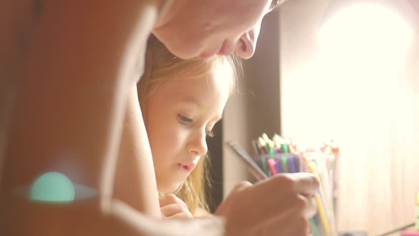 Young mother helps her daughter with her homework at on the table under the light of a lamp. Royalty-Free Stock Footage #32730967