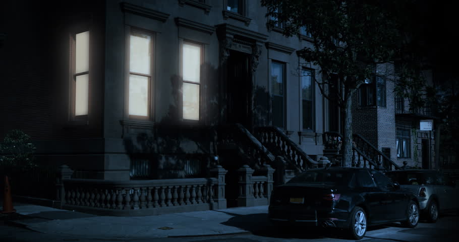 A nighttime exterior establishing shot of the first floor of a typical Brooklyn brownstone residential home as a room's windows lights up then turns off.Day/Night matching available.
