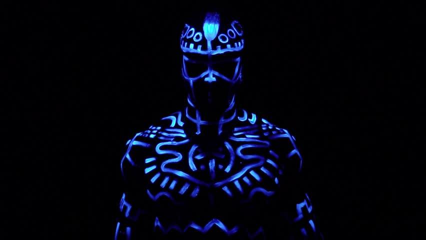 A black man in fluorescent patterns dances in ultraviolet light, slow motion