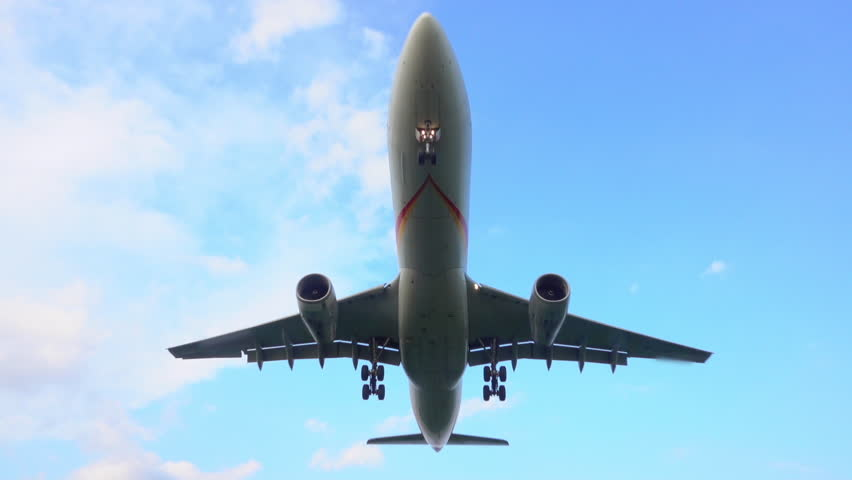 SLOW MOTION CLOSE UP: Commercial airplane flying directly over camera. Passenger airliner jet arriving and landing at large international airport. Plane taking off. Freight airplane transporting cargo
