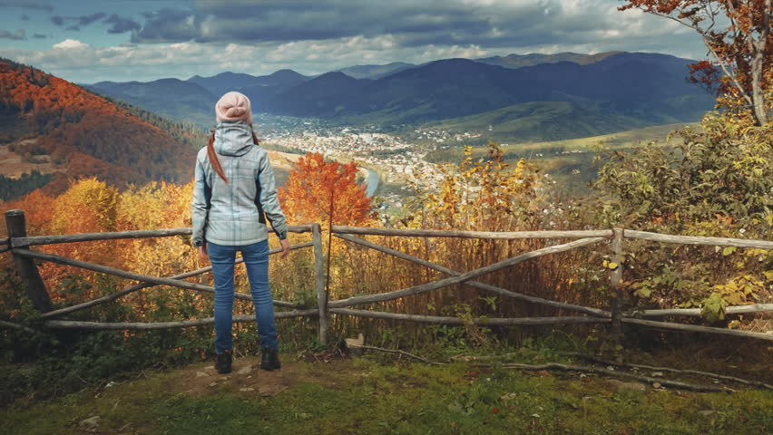 Young woman standing on the edge of the cliff and raising her hands up against mountain range and bright colorful autumn forest. Happy girl enjoying success and stunning view. Toning filter. Full HD | Shutterstock HD Video #32744968