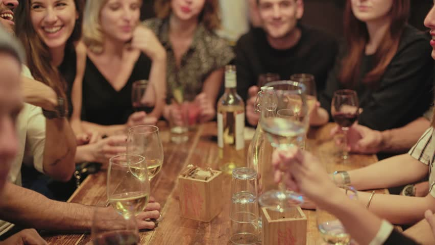 Group of happy, smiling and positive, drunk friends drink and cheer their glasses at party or reunion in middle of crowded popular hipster bar. They laugh and celebrate friendship or new year | Shutterstock HD Video #32753887