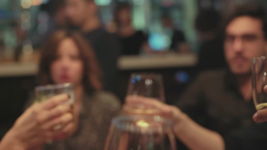 Group of friends, millennials and hipsters meet at local bar for reunion or party, toast and cheer their glasses together, full of alcohol cocktails or mixed drinks, celebrate new year