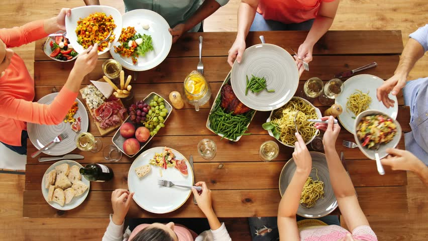Eating and leisure concept - group of people having dinner at table with food | Shutterstock HD Video #32760778