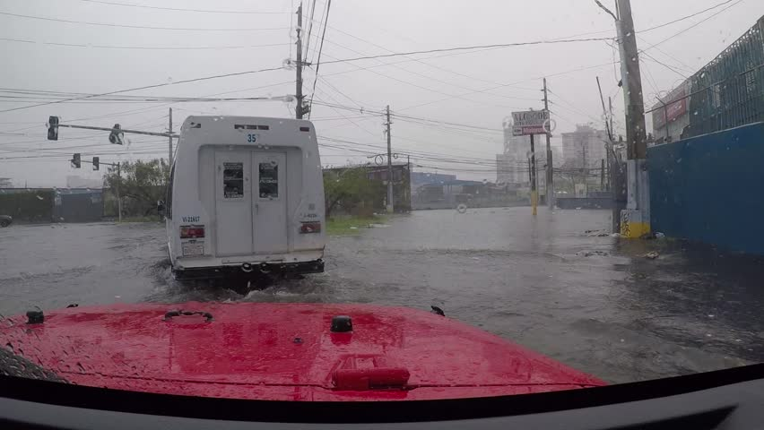 San Juan, Puerto Rico - October 03, 2017: Cars drive through flooded road section in San Juan city, Puerto Rico #32765476