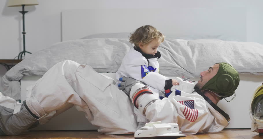 Romantic and family moments of dad and daughter playing with spacecraft, both dressed as astronauts and are happy at this unique moment. Concept of: love, family, home, games. | Shutterstock HD Video #32778646