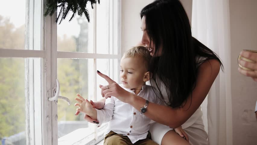 Young mother is sitting with her son on the window sill decorated with Christmas wreath and looking outside. They are talking and smiling. Happy family at home #32788465
