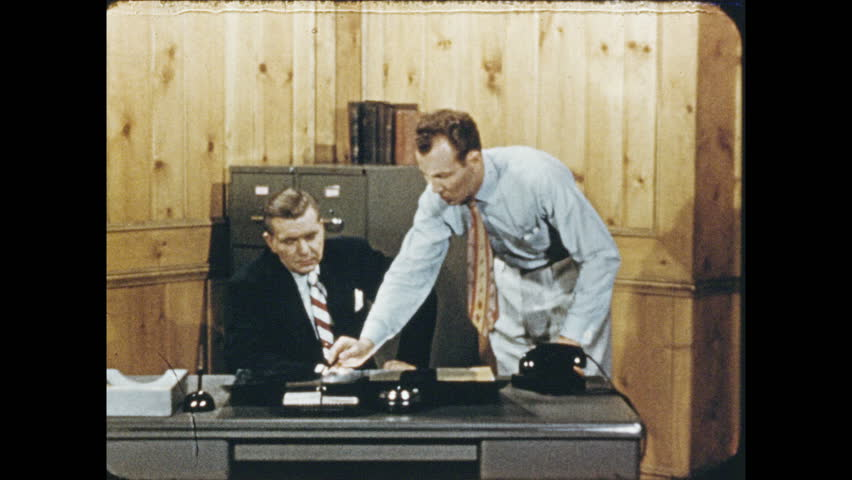 1950s: Men talking in office. Men in office, man stands and exits, zoom in to picture on wall. Torch cuts metal bar. Man takes metal piece from machine. #32792881