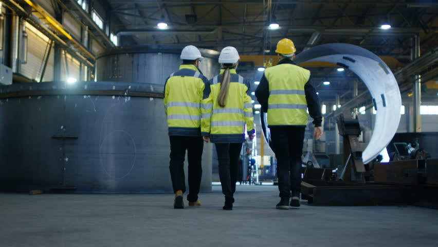 Following Shot of Three Engineers Walking Through Heavy Industry Manufacturing Factory. In the Background Welding Work in Progress, Various Metalwork, Pipeline/ Barrel Components. Slow Motion.