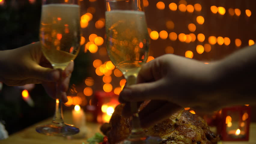 Two people raise glasses of sparkling champagne,toasting and clinking at a celebration at the dinner table with a toasted bird against the background of yellow electric lights. | Shutterstock HD Video #32794111