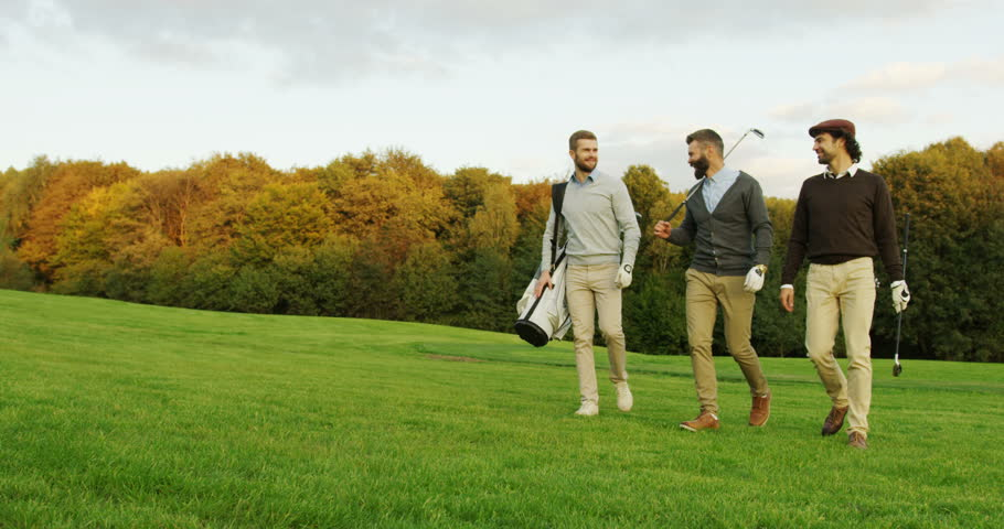 Attractive male friends walking with their clubs and bag on the golf pitch, talking and laughing. Three men having fun together playing golf.