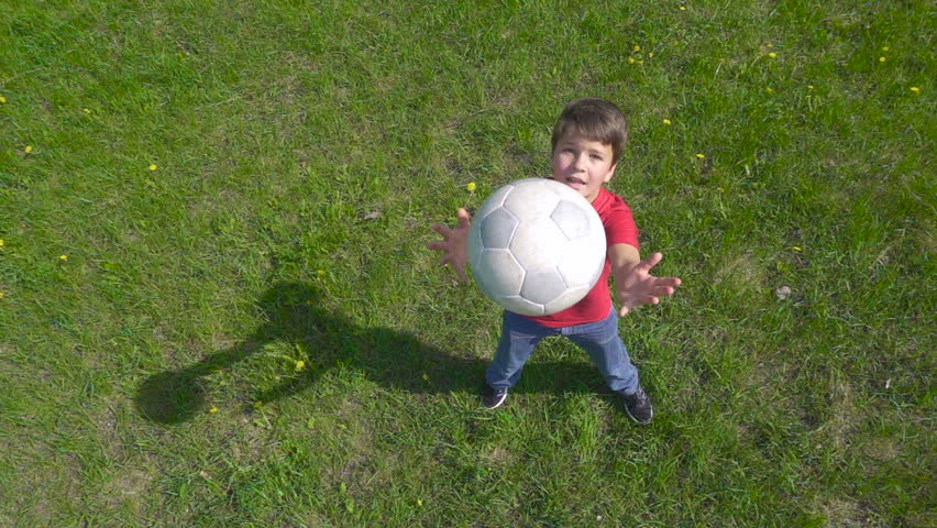 Boy throws up the ball, standing on green lawn, above view, slow motion 250 fps | Shutterstock HD Video #32809078