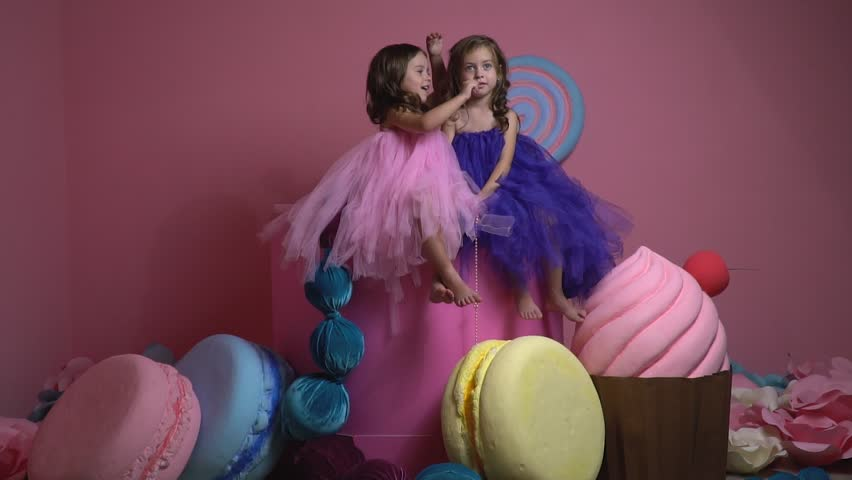 Barefoot girls in dresses sit among decorative candies and tell each other secrets, slow motion