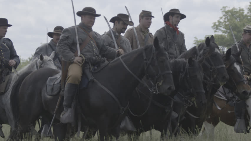 VIRGINIA - MAY 2017 - large-scale, epic Civil War anniversary reenactment -- before battle. Confederate Cavalry and officers ride horses across tall grass field with swords, flags and muskets.