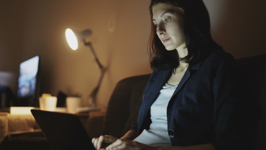 Young cheerful woman working in office at night using laptop computer and typing message | Shutterstock HD Video #32837155