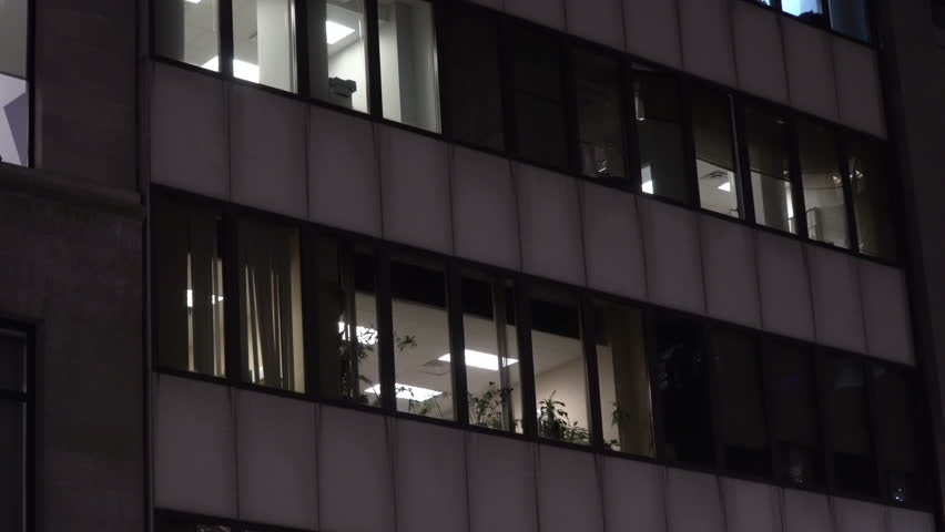 NX Night time establishing shot urban city office or apartment building exterior. Lights on through windows on skyscraper facade. Day / Night matching shot