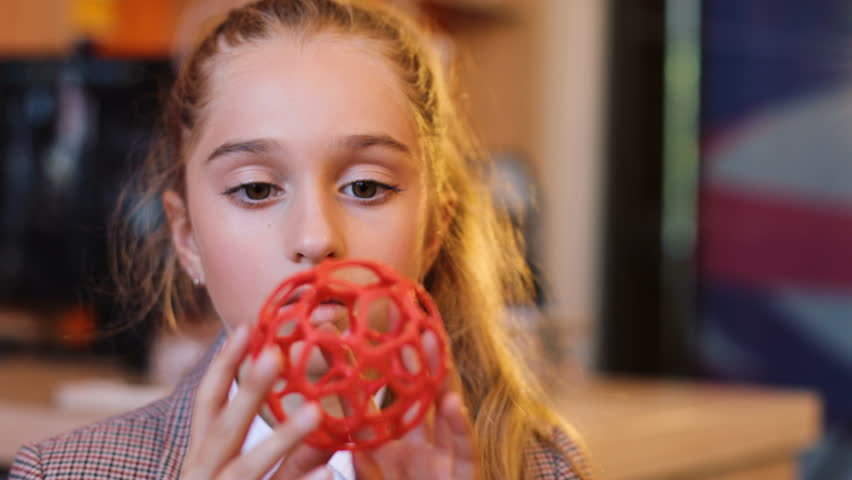 Close up of a pretty blonde girl holding a plastic red sphere and looking at it. 3D print. Indoor. Portrait shot
