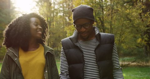 Happy lovely young African American couple walking through the park and talking in early fall. Sunny day. Outdoor