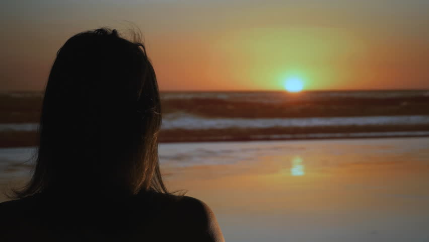 Woman looks out at Costa Rican sunset. Bare shoulders. Sea breeze blowing in her hair. Studio shot using projection, lights and fan.  | Shutterstock HD Video #32854453