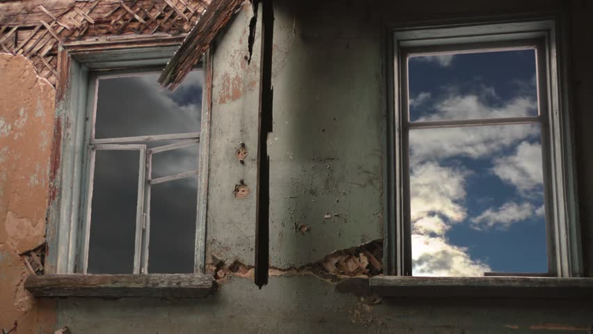 Abandoned and ruined building. Windows of the house and clouds