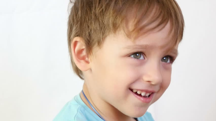 A close-up of a child who laughs happily, then closes his mouth with his hands. The boy shows joy and a smile, positive emotions. #32863957
