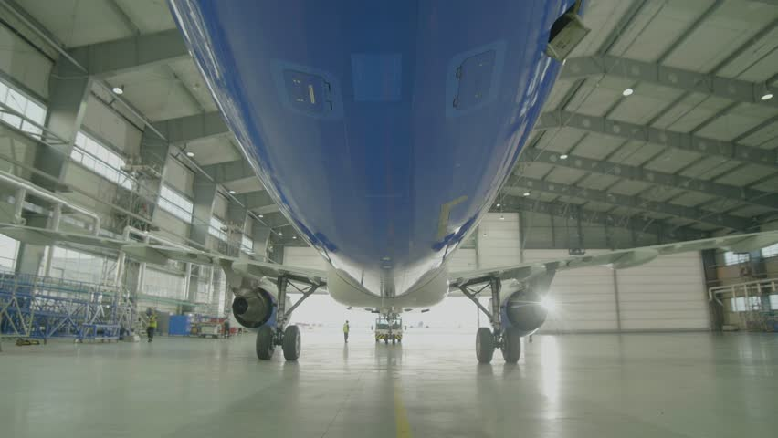 Airplane in hangar, rear view of aircraft and light from windows. Large passenger aircraft in a hangar on service maintenance