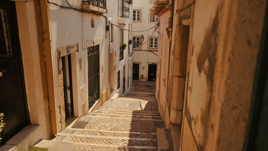 Walking along the picturesque streets of Alfama, the oldest district of Lisbon, Portugal. Alfama boasts many historical attractions along with Fado bars and restaurants. Royalty-Free Stock Footage #32870152