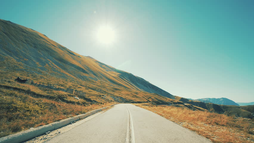 Driving On An Alpian-Like Sunny Mountain Pass Twisty Road.Pov drive on the winding roads of an Alpian mountain landscape on a sunny bright autumn day with the sun in view  | Shutterstock HD Video #32874643