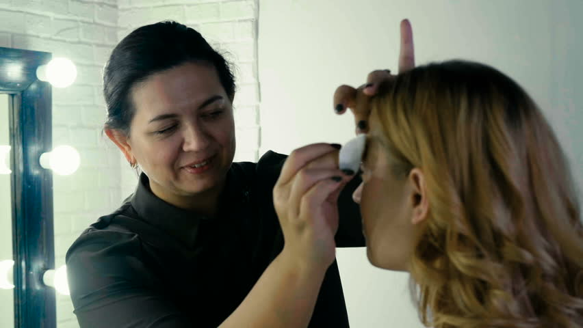 The beauty-master does the makeup of an beautiful girl, in the dressing room   Shutterstock HD Video #32885743