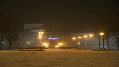 Historical brick walls of Kremlin of Veliky Novgorod, Russia at night in blizzard winter. Inscription in russian Happy NEW YEAR