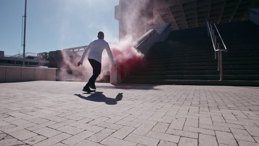 Free runners with smoke grenades performing parkour in urban space. People doing parkour tricking and freerunning in the city.