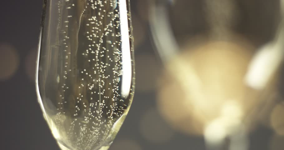 Close up video of pouring sparkling wine into a chilled glass on gray backround with blurred lights